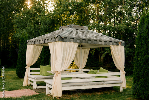 Fotografija Summer gazebo terrace with outdoor sofas made of white wood, roof and curtains