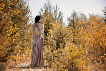 Kobieta w długiej sukni przy drzewach