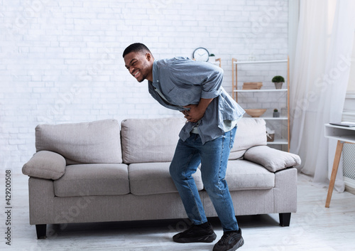 Photo Black Man Having Stomachache Suffering From Abdominal Spasm At Home