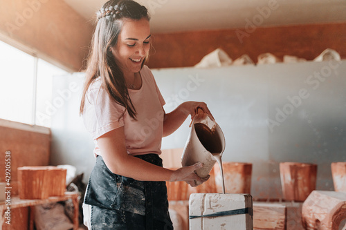 Fotografía Pottery woman in her 30s in her workshop putting cement in a mold to later make