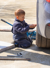 A Little Boy Fixes A Car, Changes A Wheel, Helps His Dad.