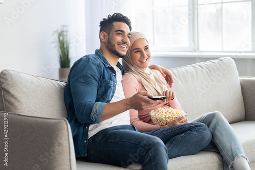 Tela Joyful arab couple watching TV together at home
