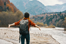 A Traveler With A Backpack In A Sweater And Jeans Are Resting In The Mountains In Nature Near The River In Autumn