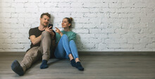 Couple Sitting On Floor By The Wall At Empty Room And Using Phone To Choose Furniture Online. Moving To New Home Concept