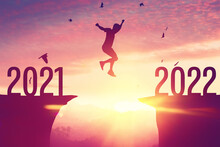 Silhouette Man Jumping And Birds Flying Between Cliff With Number 2021 To 2022 At Top Of Mountain On Sunset Sky Background.
