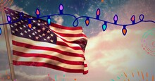 Composition Of Fairy Lights Over American Flag With Clouds On Blue Sky