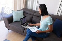 Mixed Race Transgender Woman Working At Home Using Laptop