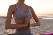 Mid Section Of Caucasian Woman Meditating And Practicing Yoga At The Beach