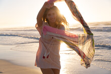 Portrait Of Caucasian Woman Holding Scarf Smiling While Standing At The Beach