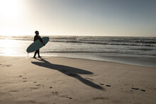 Senior Woman Walking On Beach Holding Surfboard Looking Out To Sea