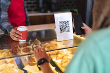 Mid Section Of Two Mixed Race Male Taking Picture Of Qr Code And Passing Coffee