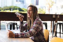 Smiling Mixed Race Man With Dreadlocks Sitting At Table Outside Cafe Talking On Smartphone