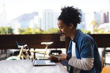 Smiling Mixed Race Man With Moustache Sitting At Table Outside Cafe Using Laptop
