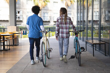 Two Mixed Race Male Friends Wheeling Bicycles In The Street And Talking