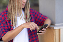 Mid Section Of Mixed Race Male With Dreadlocks Using Smartphone In The Street