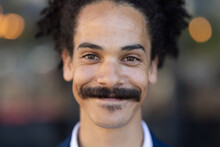 Portrait Of Mixed Race Male With Moustache Looking To Camera And Smiling