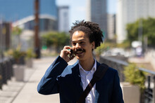 Happy Smartly Dressed Mixed Race Man With Moustache Talking On Smartphone In Street