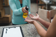 Midsection Of Female Receptionist Disinfecting Hands Of A Female Customer Over The Counter At Gym