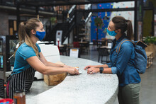 Two Happy Caucasian Women Wearing Masks Passing Cup Of Coffee Over Counter