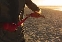 African American Man Exercising Outdoors Wrapping Hands In Preparation For Training At Sunset