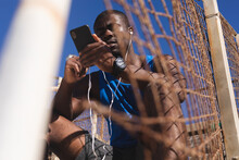 African American Man Exercising, Wearing Headphones, Using Smartphone On Sunny Day
