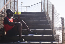 African American Man Exercising, Resting, Drinking Water On Stairs On Sunny Day
