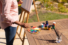 Midsection Of African American Woman Painting In A Sunny Garden