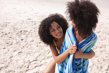 African American Mother And Daughter Wrapping With A Towel At The Beach Smiling