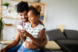 Happy father and daughter having fun with smartphone, smiling at funny video, playing mobile game