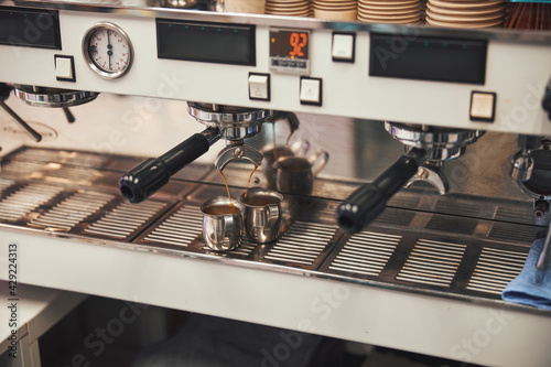 Fotografie, Obraz Aromatic espresso dripping into two cups from the coffee machine