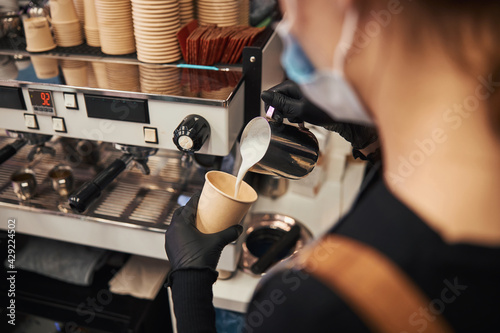 Canvas Young barista making a perfect latte for her customers
