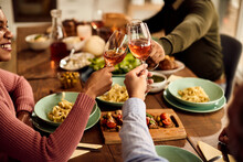 Close-up Of Friends Toasting With Wine During Lunch At Dining Table.