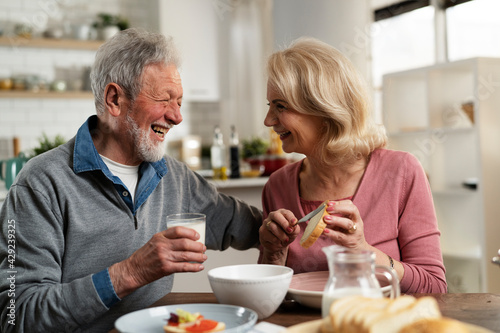 Senior couple eating breakfast in the kitchen. Husband and wife talking and laughing while eating a sandwich... - fototapety na wymiar