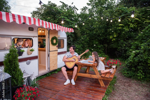 Young father plays the guitar to family. Red-haired woman mother and son look out the trailer window. Daughter listens to the song laughs. Summer fun trips with the whole family. Picnic Rest on nature