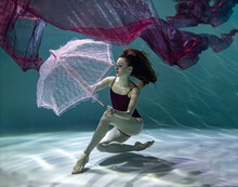 Beautiful Girl In A Red Swimsuit With A Pink Umbrella And A Red Pareo Underwater On A Blue Background