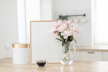 Vertical Frame And Gift Box Mockup On A Wooden Table In The Kitchen. Glass Vase With A Bouquet Of Pink Peonies And A Cup Of Black Coffee. Scandinavian Style Interior.