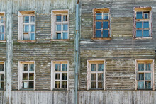 Wall Background Of Old Ramshackle Wooden House With Many Windows