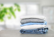 Cotton Folded Clothes On Table Indoors. Clean Apparel Stacked. Stack Of Clothing.