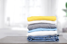 Stack Of Cotton Colorful Clothes On Table Indoors.Stacked Apparel.Folded Clean Clothing.
