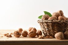 Basket Full Of Walnuts On Wood Table Isolated Background