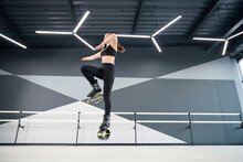 From Below View Of Active Female Teenager Doing Cardio Workout In Hall, Hi Tech Interior. Young Pretty Girl Wearing Black Sportswear Practicing Dance Moves While Doing Kangoo Jumps And Smiling.