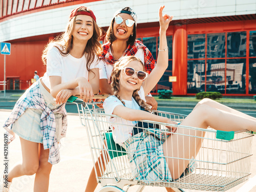 Obraz Three young beautiful female having fun in the grocery cart under the supermarket outdoors. Cheerful women racing shopping trolleys on the street background.Positive models going crazy outdoors - fototapety do salonu