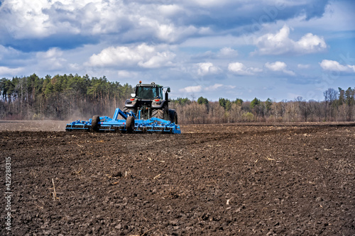 Fotografia tillage in early spring. Tractor with aggregate