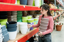 Charming Woman Choosing Ceramic Pots For Houseplants In The Garden Center. Female Buying A Pick  Planter For Transplanting Plants At Home In Warehouse