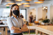 Woman business owner wearing face mask after reopening restaurant, arms folded