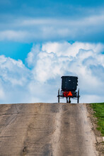 Amish Buggy At Crest Of Hill With Sky Full Of Clouds. Vertical Image.