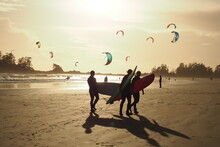 Group Of Surfers Enjoy Themselves In Foreground Of Windsurfing Enthusiasts At A Beach At Golden Hour