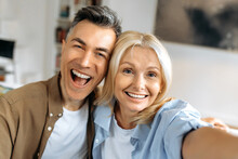Portrait Of Beautiful Cheerful Marriage Mature Couple In Casual Clothes, Caucasian Husband And Wife Taking Selfie On Smartphone, Having Fun Together, Looking At Camera, Smiling