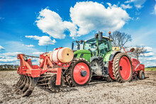 Large, Green, Modern Tractor From Germany Sowing Potatoes In The Field On A Sunny Spring Day