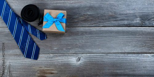 Fathers day concept with blue dress tie, belt and a giftbox on rustic wooden background